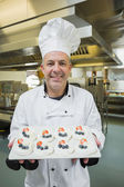 Mature chef presenting proudly plate of meringues — Foto Stock