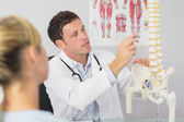 Good looking doctor showing a patient something on skeleton model — Foto de Stock
