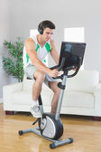 Serious handsome man training on exercise bike using laptop — Stock Photo