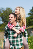 Man giving his beautiful girlfriend a piggyback ride — Stock Photo