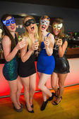 Laughing friends with masks on holding champagne — Stock Photo
