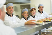 Young chefs presenting some plates to the head chef — Stock Photo