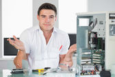 Confused computer engineer sitting behind open computer — Stock Photo