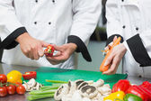 Close up of two chefs preparing vegetables — Stock Photo