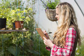 Blonde woman using a clipboard and taking notes — Stock Photo