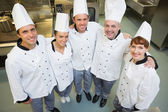 Five happy chefs smiling up at the camera — Stock Photo
