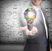 Close up of businessmans hand showing holographic light bulb — Stock Photo