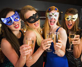 Attractive friends with masks on holding champagne glasses — Stock Photo