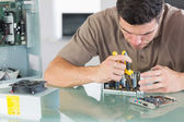 Handsome frowning computer engineer repairing hardware with pliers — Stock Photo