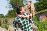 Handsome man giving his girlfriend a piggyback ride — Stock Photo