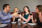 Friends clinking red wine glasses at a bar — Stock Photo