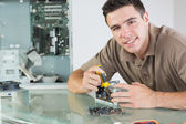 Handsome smiling computer engineer repairing hardware with pliers — Stock Photo