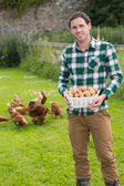 Happy man showing a basket filled with eggs — Stock Photo