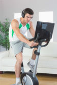 Determined handsome man training on exercise bike using laptop — Stock Photo