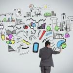 Businessman pointing at economic illustration — Stock Photo
