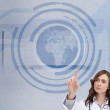 Concentrated doctor pointing at holographic globe — Stock Photo #36159235