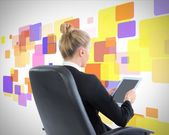 Blonde businesswoman sitting on swivel chair with tablet — Stock Photo