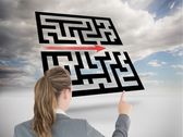 Businesswoman pointing at holographic maze — Stock Photo