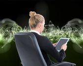 Kobieta siedzi na Krzesło obrotowe z tabletem — Zdjęcie stockowe
