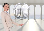 Composite image of smiling asian businesswoman pointing — Stock Photo