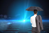 Composite image of businessman standing back to camera holding umbrella — Stockfoto