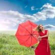 Beautiful woman wearing red dress holding umbrella — Stock Photo #36160413