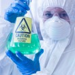 Scientist in protective suit with hazardous chemical in flask — Stock Photo #36166841