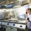 Young happy chef standing next to work surface phoning — Stock Photo