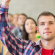 Close-up of a male student raising hand by others in classroom — Stock Photo