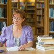 Mature female student studying at desk in the library — Stock Photo