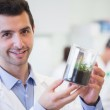 Smiling male researcher holding young plant at lab — Stock Photo #36167051