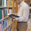 Handsome man reading concentrated a book standing in library — Stock Photo #36167069