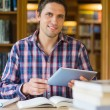 Happy mature student holding tablet PC in the library — Stock Photo