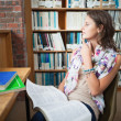 Thoughtful female student with a book in the library — Stock Photo #36167287