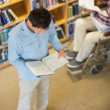 Stock Photo: Man and disabled student in wheelchair reading books in library