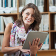 Happy student using tablet PC against bookshelf in library — Stock Photo #36167395