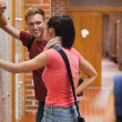 Foto Stock: Students leaning against locker flirting