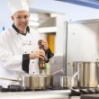 Stock Photo: Smiling head chef flavoring food with pepper