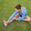 Sporty woman stretching her leg while sitting on the grass — Stock Photo