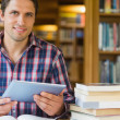 Mature student holding tablet PC in the library — Stock Photo