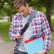 Handsome casual student standing and texting — Stock Photo #36167475