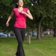 Stock Photo: Happy woman running in a green park