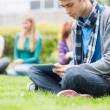 College boy using table PC with blurred students in park — Stock Photo
