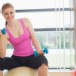 Fit smiling woman with dumbbells sitting on exercise ball — Stock Photo