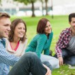Casual happy students sitting on the grass laughing — Stock Photo