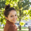 Cute brunette woman wearing a brown coat posing in a park — Stock Photo #36168063