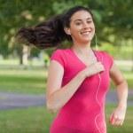 Motivated pretty woman jogging in a park — Stockfoto