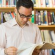 Concentrated mature student reading book in library — Stock Photo #36168131