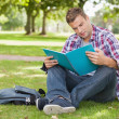 Handsome concentrating student sitting on grass studying — Stock Photo #36168145