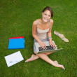 Female student using laptop with books at the park — Stock Photo #36168227